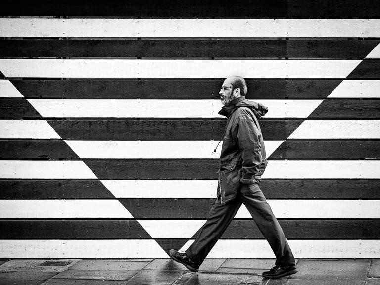 A man walks in front of a dramatically painted wall, his stride matching the pattern behind him